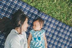 Maman et fille dans les happines s'étendant sur une herbe Image libre de droits