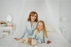Maman et fille dans les mêmes pyjamas sur le lit Regard de famille photos libres de droits