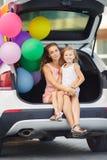 Maman et fille dans une voiture avec des ballons Photographie stock libre de droits