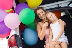 Maman et fille dans une voiture avec des ballons Images stock