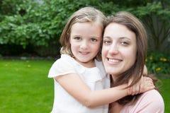 Maman et fille de portrait dans les happines à l'extérieur dans le pré Images stock