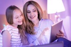Maman et fille de sourire détendant ensemble Photo stock