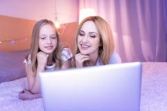 Maman et fille de sourire regardant l'ordinateur portable Image stock