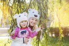 Maman et fille en parc, dans un sourire tricoté de chapeau Photos libres de droits