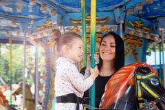 Maman et fille en parc et tour sur le carrousel Photos stock