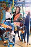 Maman et fille en parc et tour sur le carrousel Images stock