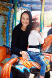Maman et fille en parc et tour sur le carrousel Photographie stock libre de droits