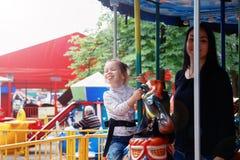 Maman et fille en parc et tour sur le carrousel Image libre de droits
