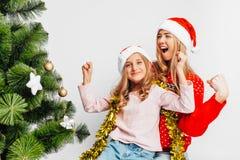 Maman et fille heureuses, dans des chapeaux de Santa, se reposant près du Christ photographie stock libre de droits
