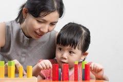 Maman et fille jouant le bloc en bois pour créer une imagination Images stock