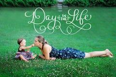 Maman et fille jouant sur l'herbe verte dans un jour de pré et de textes pendant la vie Aspiration de main de vintage de lettrage Photos stock