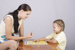 Maman et fille jouant un jeu de société Photographie stock libre de droits