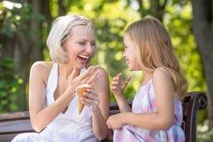 Maman et fille mangeant la crème glacée ensemble Images stock