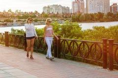 Maman et fille parlant, souriant, marchant par le parc de ville Image stock