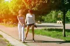 Maman et fille parlant, souriant, marchant par le parc de ville Images libres de droits