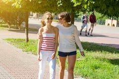 Maman et fille parlant, souriant, marchant par le parc de ville, le jour d'été Photographie stock libre de droits