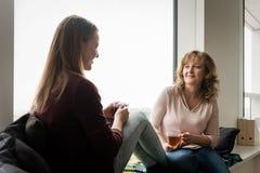 Maman et fille parlant tout en ayant une tasse de thé Photos stock