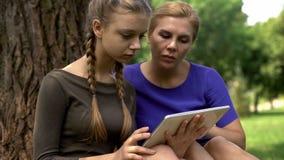 Maman et fille passant en revue des programmes d'université sur le comprimé pour s'appliquer, services en ligne image stock