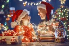 Maman et fille près d'arbre de Noël Photographie stock libre de droits