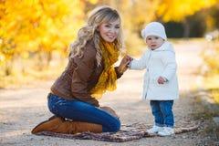 Maman et fille se reposant en parc en automne Photographie stock libre de droits