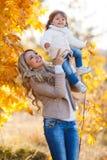 Maman et fille se reposant en parc en automne Image stock