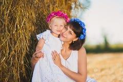 Maman et fille un jour joyeux d'été de meule de foin Images stock