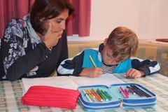 Maman et fils étudiant à la maison Photographie stock libre de droits