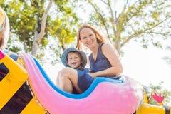 Maman et fils ayant l'amusement à un parc d'attractions Image libre de droits
