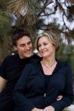 Maman et fils heureux par l'arbre de pin Photographie stock libre de droits