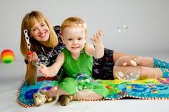 Maman et fils jouant avec des bulles de savon Image stock