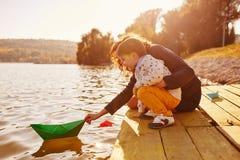 Maman et fils jouant avec les bateaux de papier par le lac Photographie stock