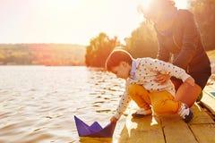 Maman et fils jouant avec les bateaux de papier par le lac Images libres de droits