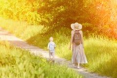 Maman et fils marchant le long de la route en parc Vue arrière Jour ensoleillé Photos stock