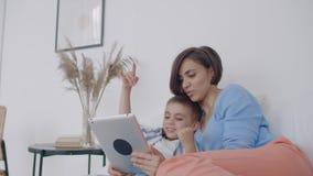 Maman et fils regardant l'écran de comprimé se trouvant sur un lit blanc Jeux de jeu avec votre fils sur votre tablette et clips vidéos