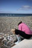 Maman et fils s'asseyant sur la plage Photo stock