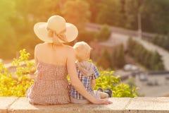 Maman et fils s'asseyant sur le fond de la forêt verte et du village loin Images libres de droits