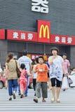 Maman et fils sur un passage clouté avec le débouché de MacDonald sur le fond, Xiang Yang, Chine Photographie stock