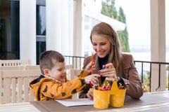 Maman et jeune crayons colorés de garçon par aspiration Image libre de droits