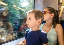 Maman et jeune fils dans un train électrique Images libres de droits