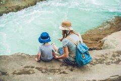 Maman et jeune fils s'asseyant sur le pont sur un fond de la rivière Photos libres de droits