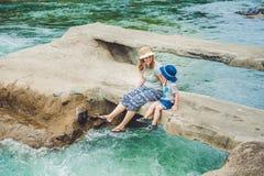 Maman et jeune fils s'asseyant sur le pont sur un fond de la rivière Photos stock