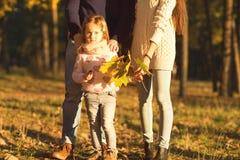 Maman et papa avec la fille à jouer de coucher du soleil Image libre de droits