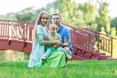 Maman et papa avec la petite fille en parc Photographie stock