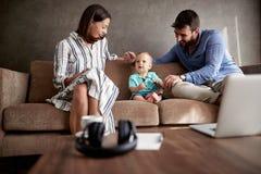Maman et papa heureux avec leur livre a de jouer et de lecture de bébé garçon photo libre de droits