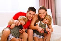 Maman et papa jouant avec le descendant sur la console Photos libres de droits