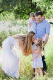 Maman et papa jouant sur la nature et étreignant deux filles Photo libre de droits