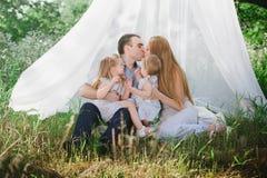 Maman et papa jouant sur la nature et étreignant deux filles Photographie stock libre de droits