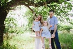 Maman et papa jouant sur la nature et étreignant deux filles Image libre de droits