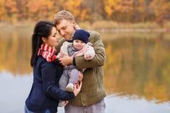Maman et papa tenant le bébé dans des mains Images stock
