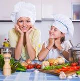Maman et petite fille faisant cuire le plat vegeterian à l'intérieur Photographie stock libre de droits